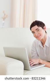 Cute Woman lying on a sofa with a laptop in the living room