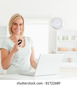Cute woman with a mobile and a laptop smiling into the camera in the kitchen
