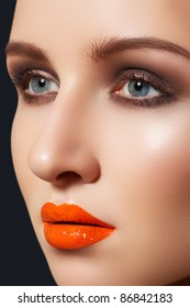 Cute woman model with bright fashion make-up. Sexy lip gloss makeup, dark shadows on eyelids, fresh clean complexion
