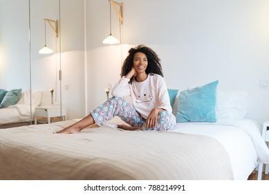 cute woman on bed smiling wearing pyjama