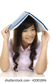 Cute woman with opened book on head.