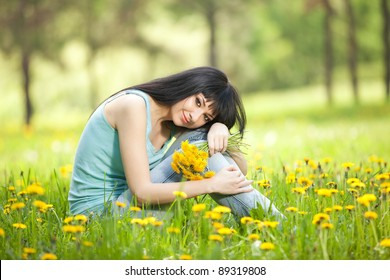 Cute woman in the park with dandelions