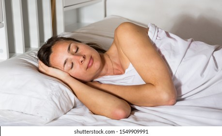 Cute woman in pygama sleeping in bed in bedroom at home interior