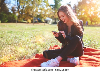 Cute woman is reading pleasant text message on mobile phone while sitting in the park in warm spring day,gorgeous female is listening to music  and searching information on cell telephone