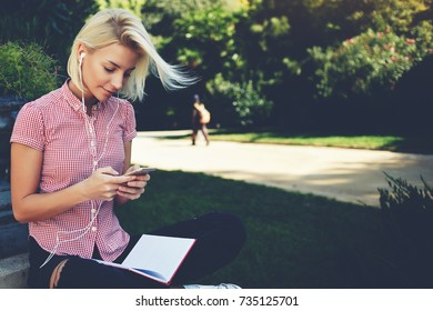 Cute woman is reading pleasant text message on mobile phone while sitting in the park in warm spring day,gorgeous female is listening to music in headphones and searching information on cell telephone