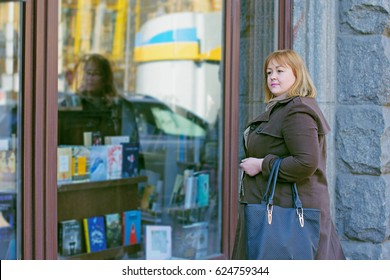 Cute woman with red hair of size plus size walks through the  margins looks in showcases chooses things like shopping and beautiful stylish accessories reflects on her appearance