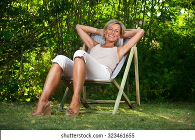 Cute woman relaxing on a deckchair outdoor in her  garden