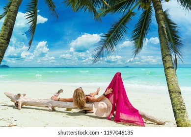 Cute woman relaxing on the summer beach at the tropical resort