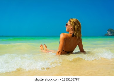 Cute woman relaxing on the summer tropical beach. winter vacation in Paradise.