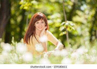 Cute woman rest in the park with dandelions