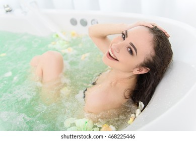 Cute woman resting in whirlpool bath