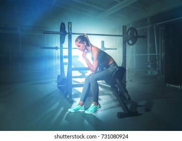 The cute woman sit on a bench in the gym on a bright light background