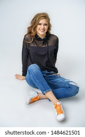 cute woman with sitting in jeans on white background and smiling.