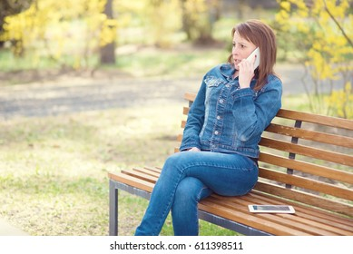 Cute woman sitting on the bench in the park