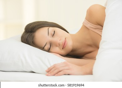 The cute woman sleeping on the bed