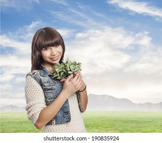 cute woman smiling and holding a plant