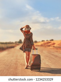 Cute woman in summer dress and hat hitchhiking with suitcase at autumn toned. Female walking on the road with Luggage. Freedom concept
