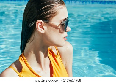 Cute woman in sunglasses yellow swimsuit in the pool vacation travel tropics