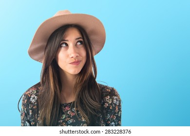 Cute woman thinking over colorful background