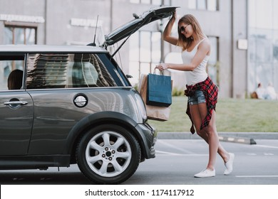 Cute Women Putting Shopping Bags into Car. Sale, Consumerism and People Concept. Shopping and Tourism Concept. Girls Bags Walking Down the Street on Sunny Day after Good Shopping.