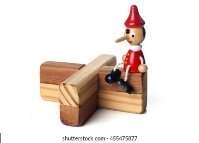 Cute wooden doll of Pinocchio liar with big nose seated on a wooden structure over white background.