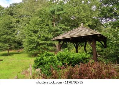 Cute wooden gazebo in a beautiful, lush park. Summer season.