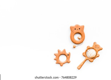 Cute wooden handmade toys for newborn on white background top view copyspace