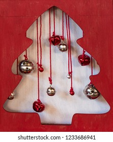 Cute wooden holiday curio box with red and silver bells hanging inside the silhouette of a Christmas tree.