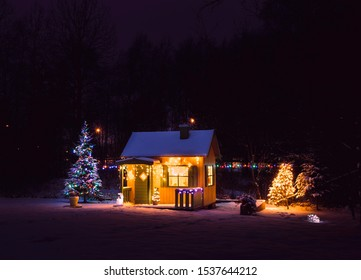 Cute, wooden painted yellow private children`s play house in home garden, decorated with Christmas LED string lights outdoors in cold snowy winder night. Decorated Christmas fir tree.