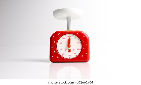 Cute wooden red strawberry shape kitchen scales. Isolated on white background. Slightly de-focused and close-up shot. Copy space.