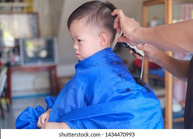 Cute worried little Asian 3 years old toddler baby boy child getting a haircut at the hairdresser's barber shop, Kid cut with hairdresser's machine