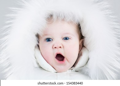 Cute yawning baby girl wearing a huge white fur hat and a warm winter jacket ready for a walk on a cold day
