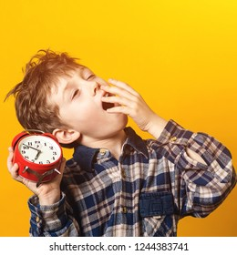 Cute yawning kid holds red alarm clock. Sleepy and yawning schoolboy over yellow wall. Funny boy yawns wide, covering his mouth with hand. Emotion concept