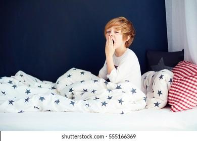cute yawning kid in pajamas sitting in bed