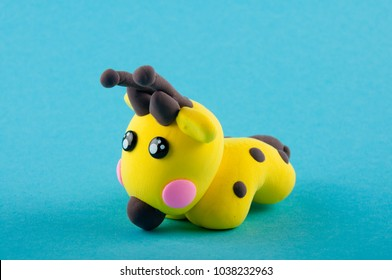 Cute yellow, brown giraffe made of modelling clay staying on blue background
