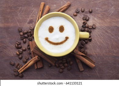 A cute yellow cup with coffee cream. Food art creative concept image, happy face drawing with cinnamon powder over wooden background.