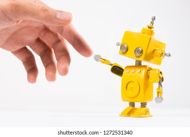 Cute, yellow, handmade robot with a human hand on a white background. Like The Creation of Adam painting of Michelangelo.
