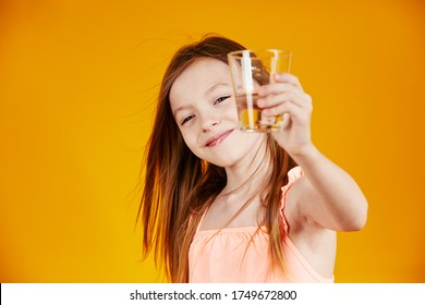 cute young 9 year old caucasian little girl with long hair smiling and drinking a glass of water on yellow studio background