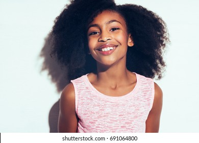 Cute young African girl with long curly hair smiling confidently while standing by herself against a gray background