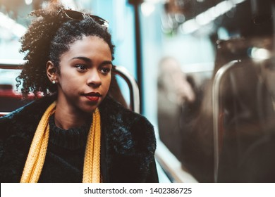 A cute young African-American female on a seat of metro in a demi-season coat and yellow scarf is thoughtfully looking into the window of a subway carriage, with a copy space area on the right
