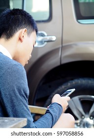 cute young asian boy with black short hairs wearing dark casual brown gray t-shirt sitting outdoor near a parked car concentration on playing game and reading message on mobile handy smart phone