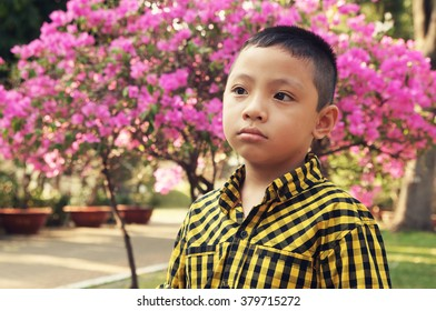 Cute young asian boy on blooming garden background with room for text