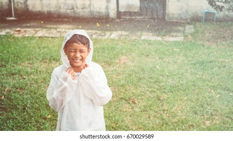 cute young Asian boy smiling and enjoying playing outside in the rain, green background