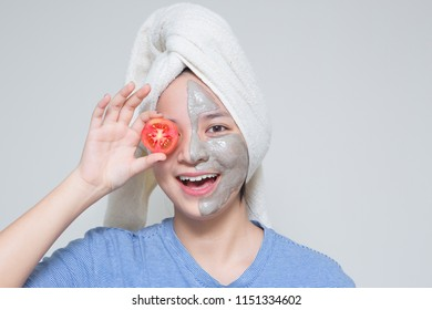 cute young Asian teenage girl hold tomato, smile happy face masking cream on face and towel on her head. woman beauty shot with idea of skin care nutrition, suitable for skin care and cosmetic product
