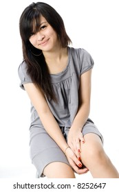 A cute young Asian teenager in grey dress on white background