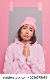 Cute young Asian woman begs you says please asks for help or favor pleads about something supplicating wears casual sweatshirt and hat has sulking expression poses indoor. Give me one more chance
