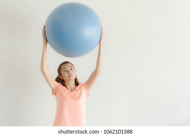 Cute Young Asian Women Used Hands Lifting Exercises Ball Stability Over White Wall. Copy Space For Text. Concepts of exercise ball exercises for beginners.
