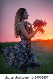 Cute young attractive girl with a bouquet of colorful flowers in her hands and a black hat. Evening walk in nature during sunset. Pensive look. Romantic atmosphere.