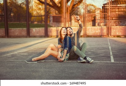Cute young beautiful couple sitting on the ground in city near university after studying and having fun together laughing and smiling