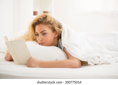Cute young beautiful woman reading book in the bed